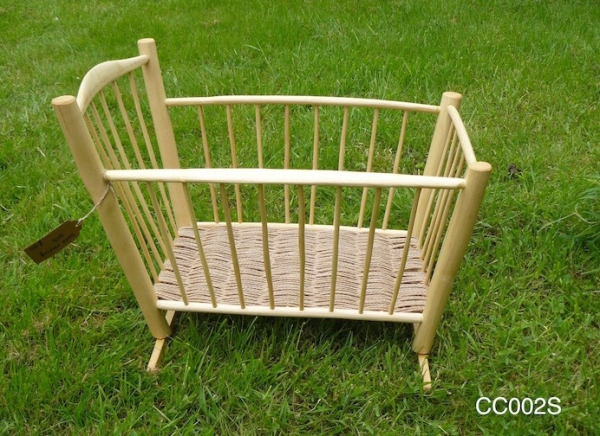 handcrafted rustic ash chair spindled baby's crib on grass background