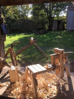 green woodworking tools, shaving horse, axe, froe with countryside view