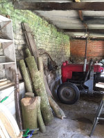 pile of ash wood logs and old red tractor at rustic ash chairs workshop