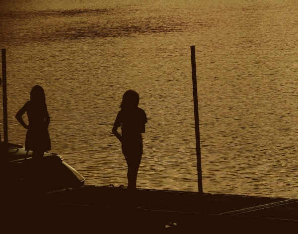 Two Girls Standing On Dock