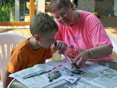 Grandma helps James clean a fish he caught – 2012