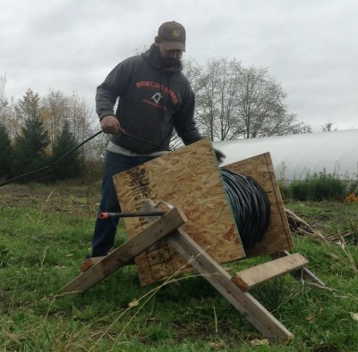 Michael rolling up drip tape on a farm made spool
