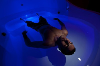 Man floating in a floatation therapy pod with a blue light
