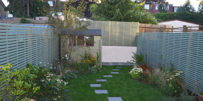 Photo of a small Chiswick garden with slatted fence panels designed by John Ward Garden Design
