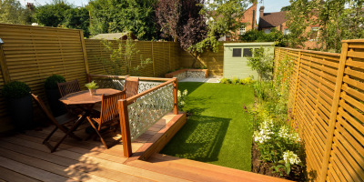 Photo showing a large dinning deck leading to the artificial lawn in this family garden in St. Albans