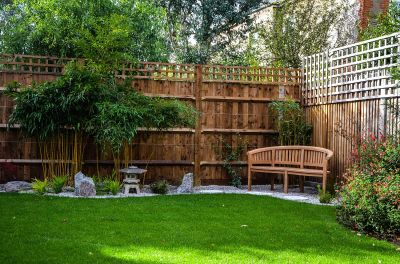 Photo of teak curved bench in corner of garden