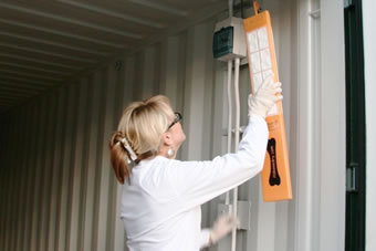 Attaching a dampstick to the wall of a self storage container in Newton Abbot