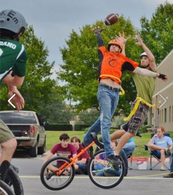 Image of two men on unicycles trying to catch an American football