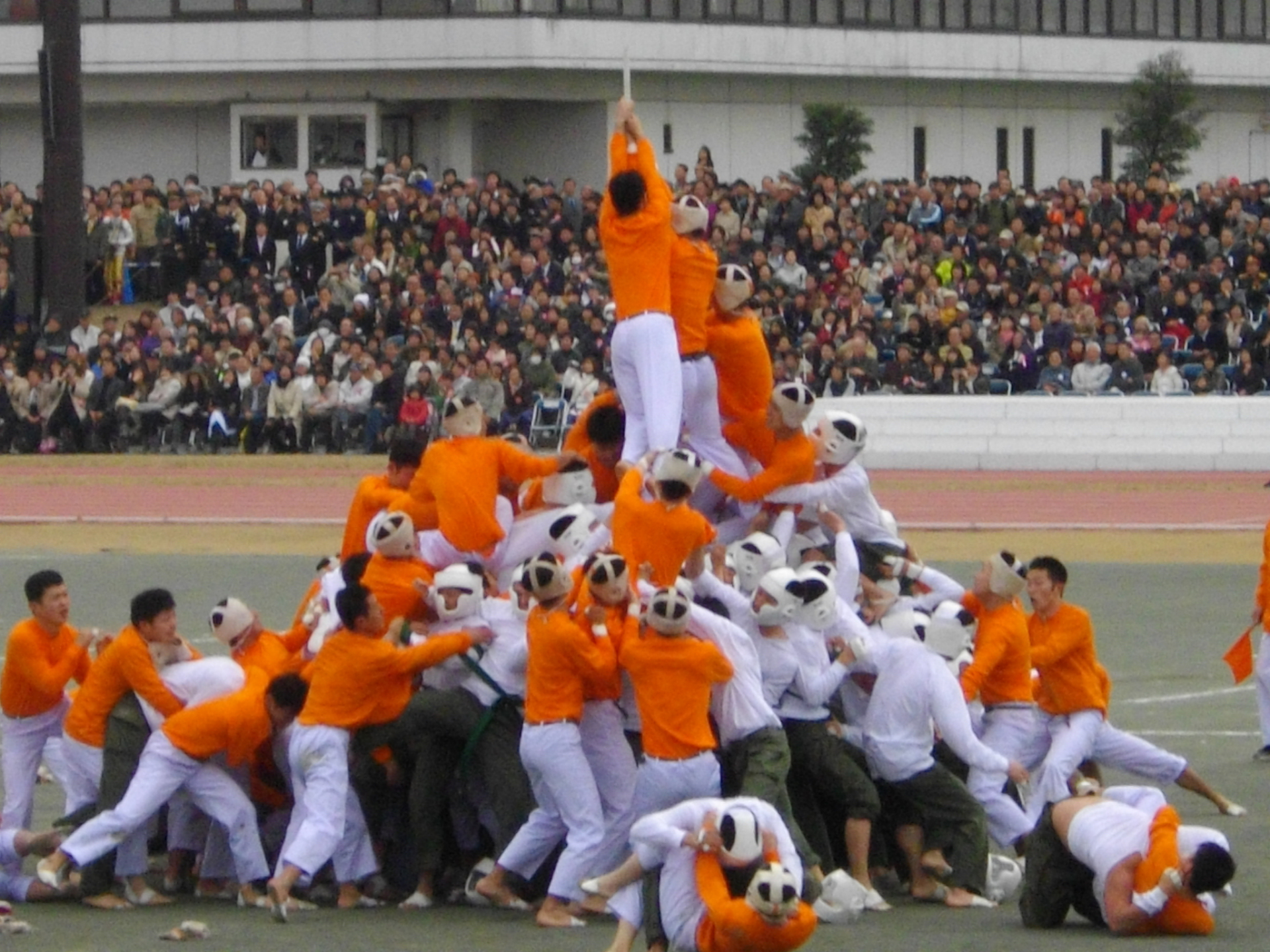 Image of 75 men climbing a pole and hanging from it.