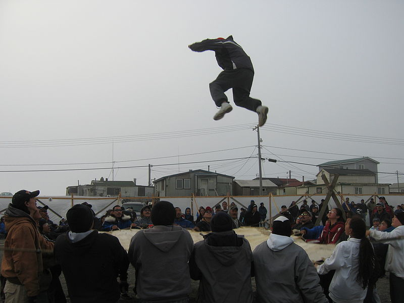 man being thrown in the air from a blanet as part of the the 'Nalukataq' festival