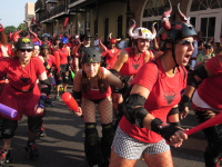 Women's roller derby players chasing after men with bats as part of the USA San Fermin celebrations
