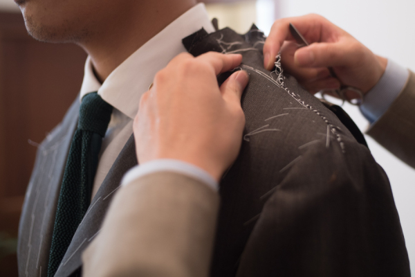 A tailor fitting a client for a new suit