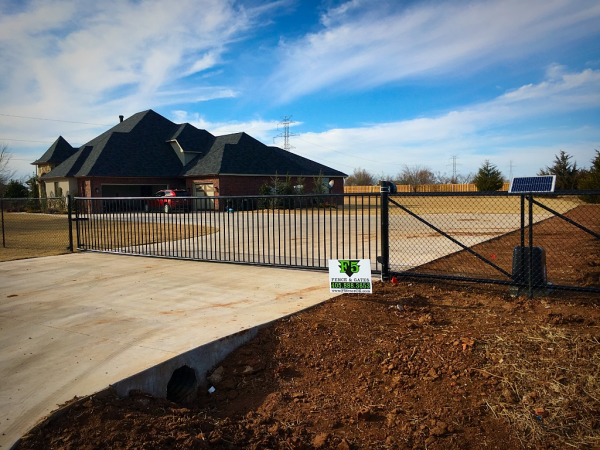 Edmond Oklahoma Fence and Gate Company Security Double Iron Gate with Solar Gate Opener Entry Access System Iphone Wireless Smart Phone Capable Emergency Shut Off Alarm Remote Keyless with Black Chain Link Fence