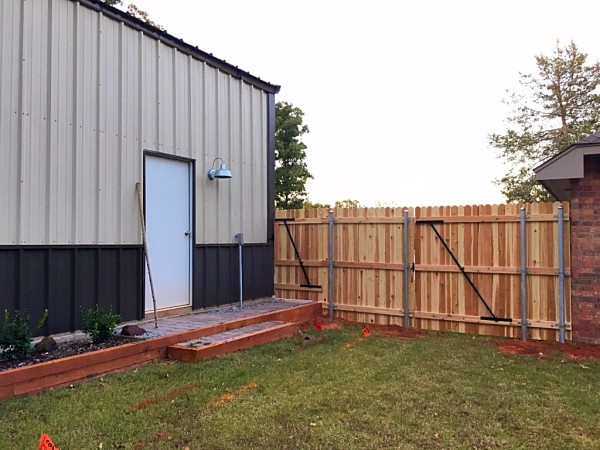 Wood shop fence with 7/8 cedar picket in Edmond Oklahoma Fence Company on steel posts, concrete and custom walk gates