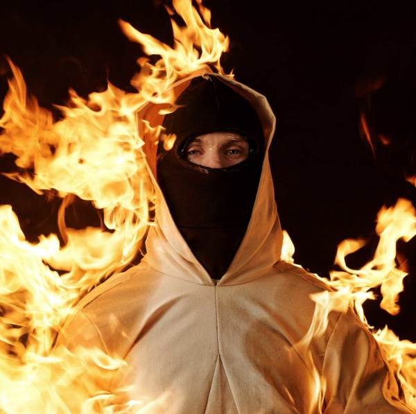 Still from Inextinguishable Fire. Person in black ski mask and yellow coat, with flames and a black