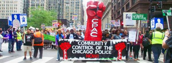 People protesting in the street, CPAC banners centered, giant red sculpture of fist w/ CPAC text