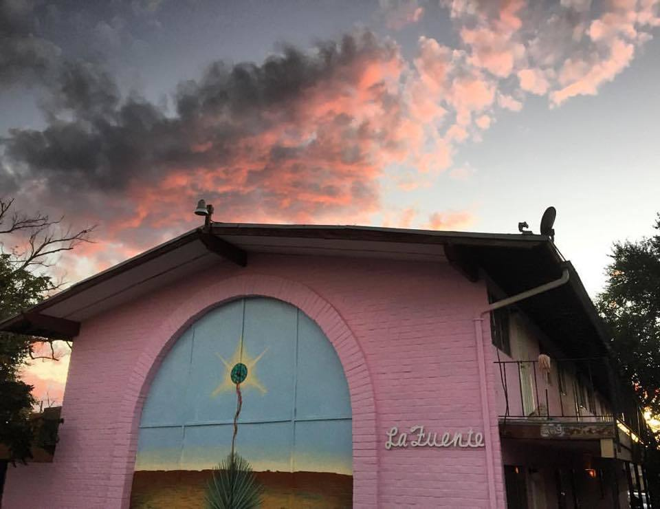 Photo of a pink building with desert scape painted in front arch, with cloudy sky reflecting sunset.