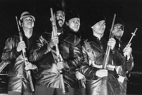 Black & white still from the movie Panther (1995) showing a group of Black Panthers, holding rifles.