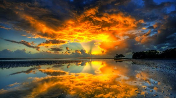 Orange sunset reflecting off of heavy clouds and a body of water.