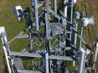 A Close up photograph of a mobile phone mast, taken from above using a drone, showing the equipment and condition of the mast
