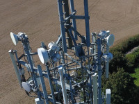 A close up photograph of the various antenna on a mobile phone mast, taken from above using a drone, showing the transmission equipment