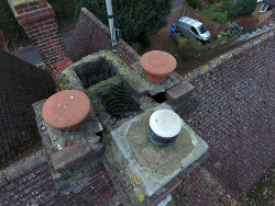 a photograph taken by a drone of the top of a chimney stack, showing the poor condition and missing bricks