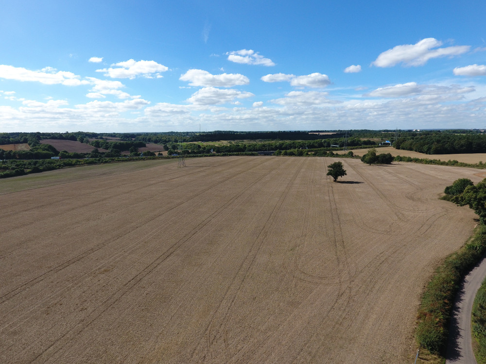 A drone photo of a harvested field, taken from a height of approximately 50 metres, showing just the stubble and combine harvester wheel tracks