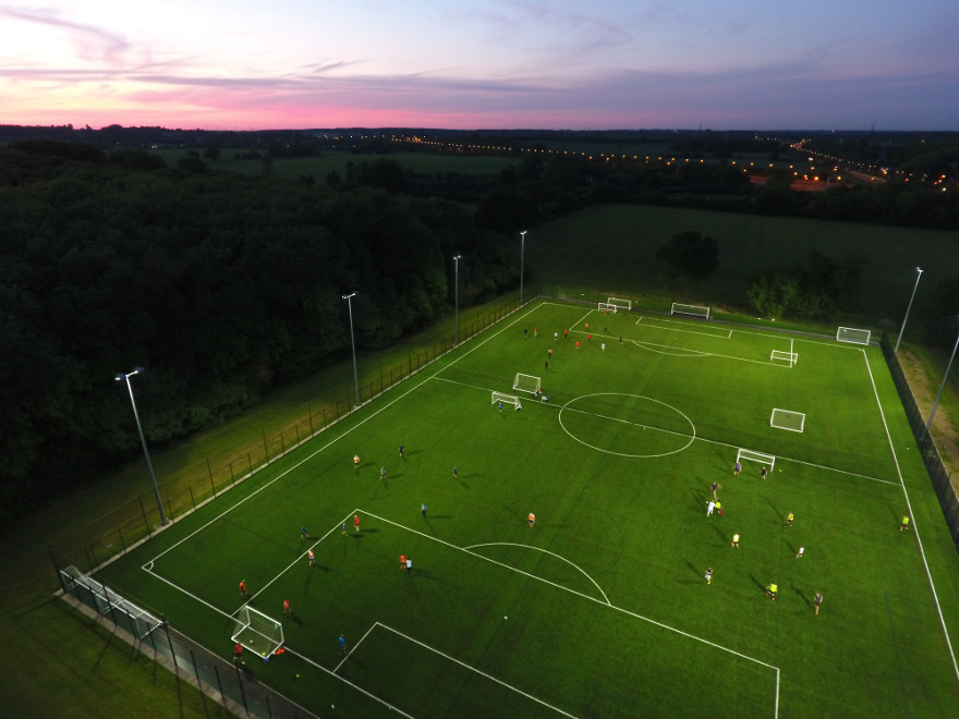 Aerial view by drone of a floodlit five a side football match at sunset.
