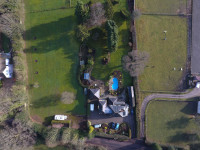 An aerial photograph, taken by a drone from above, looking directly down on a house and grounds, showing the layout and size of plot