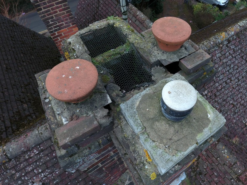 Close up photograph from above a damaged chimney stack, taken by a drone, revealing missing bricks and poor condition.