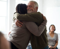 Image of two people hugging to represent community support.