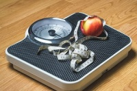 Image of scale with stethescope and apple to represent wellness promotion
