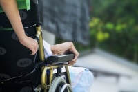 Image of a care provider pushing a wheel chair to represent respite care.