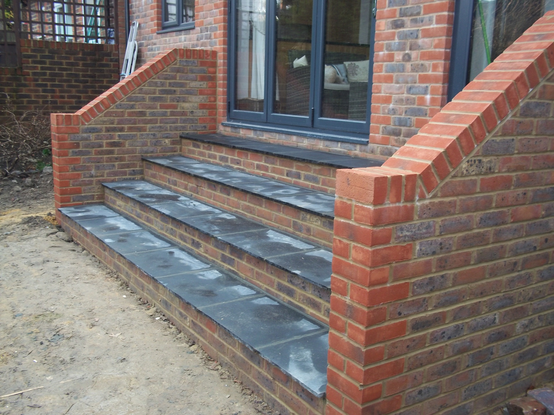 "Steps and 9"" brick walls built to match existing house."