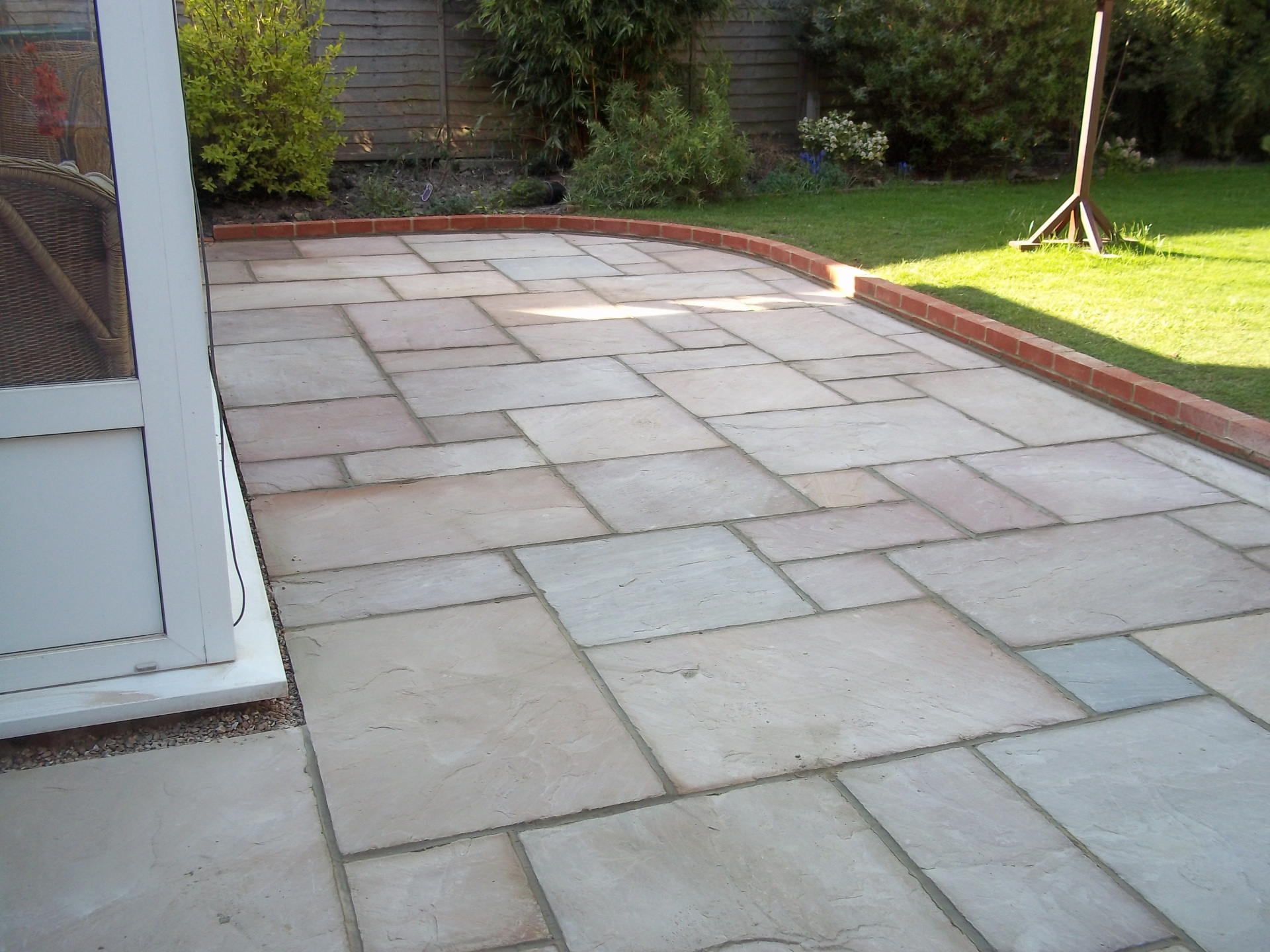 Indian sandstone patio with brick edging.