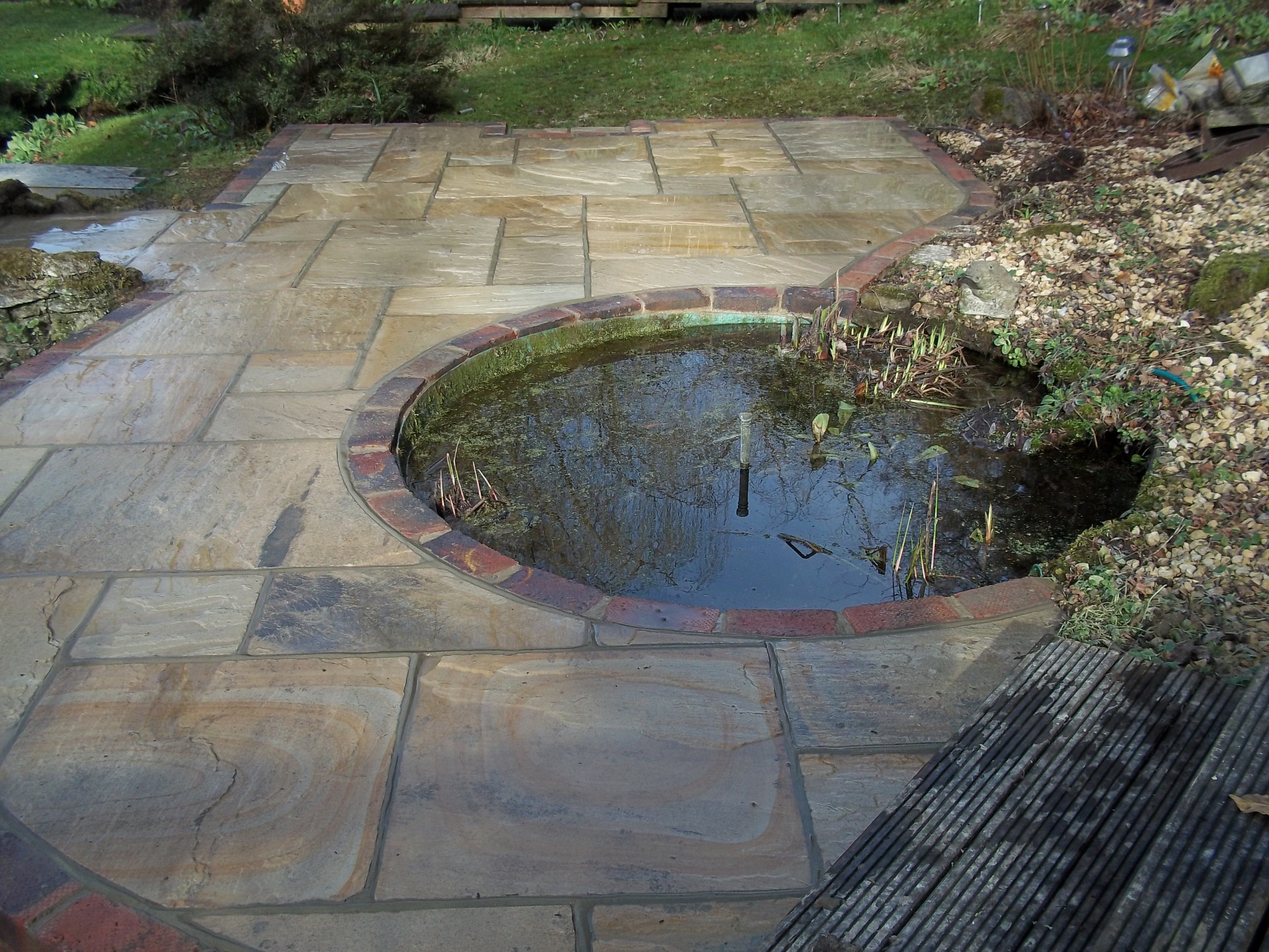 Indian sandstone patio built round fish pond.