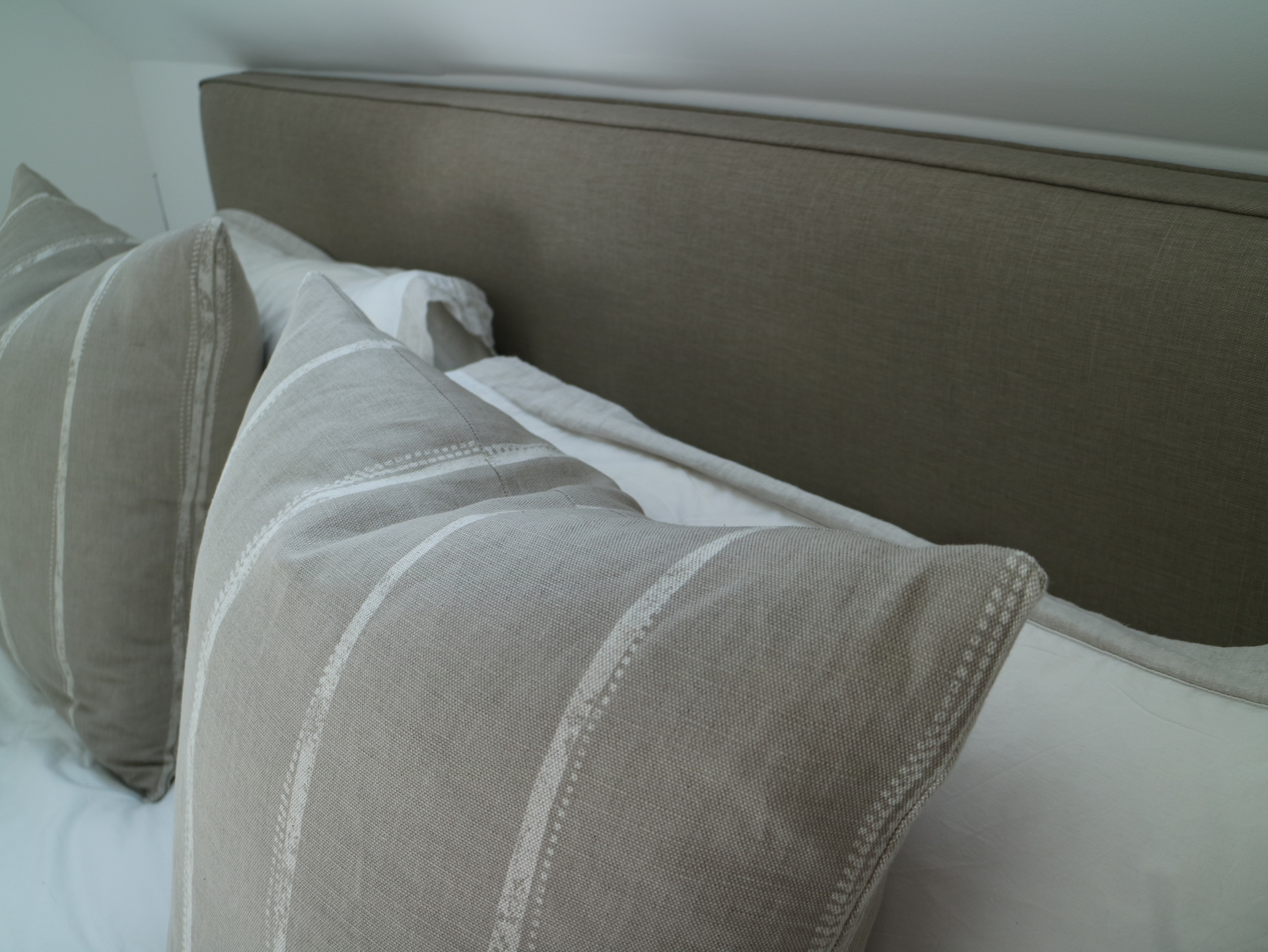 handmade headboard and cushions in natural linen by Ian mankin