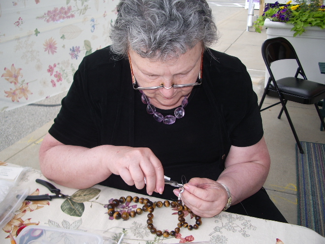 Jewelry Artist at work at her booth at show