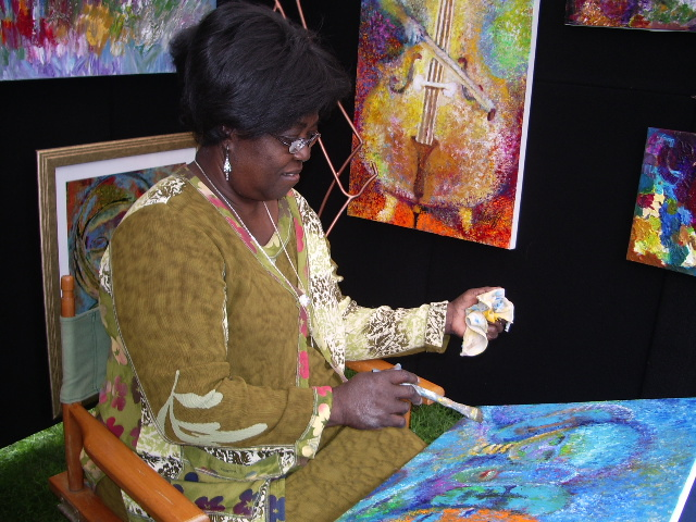 Artist working on a painting in her booth.