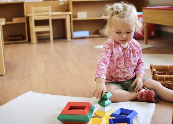 Toddler completing montessori method lesson with colors and shapes