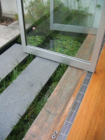 Gray Smith Architecture Barlow Residence pivot glass doors over pond and steps