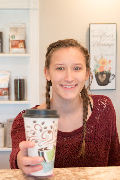 Smiling teen offers coffee