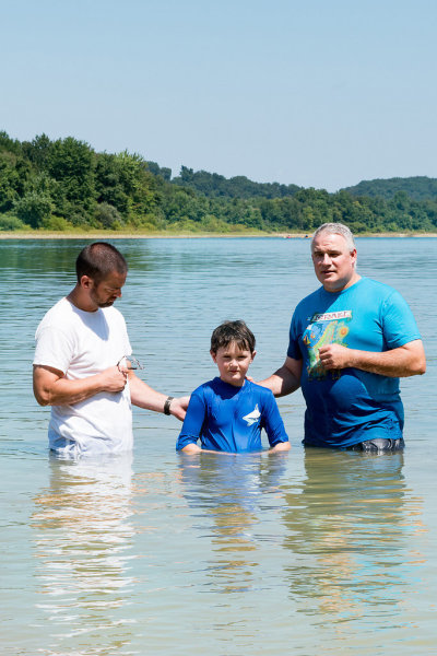 A young man is being baptized in a lake.