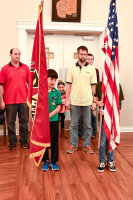 The AWANA boys stand at attention with flags.