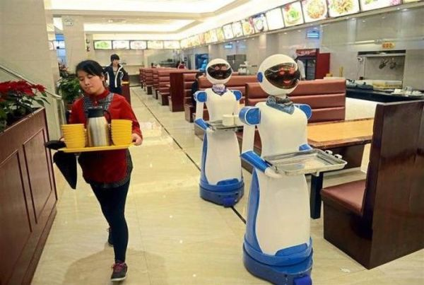 Waitress gives two server robots a wide berth