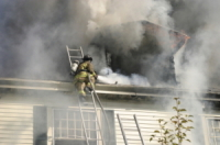 Image of fireman on roof of smoking house