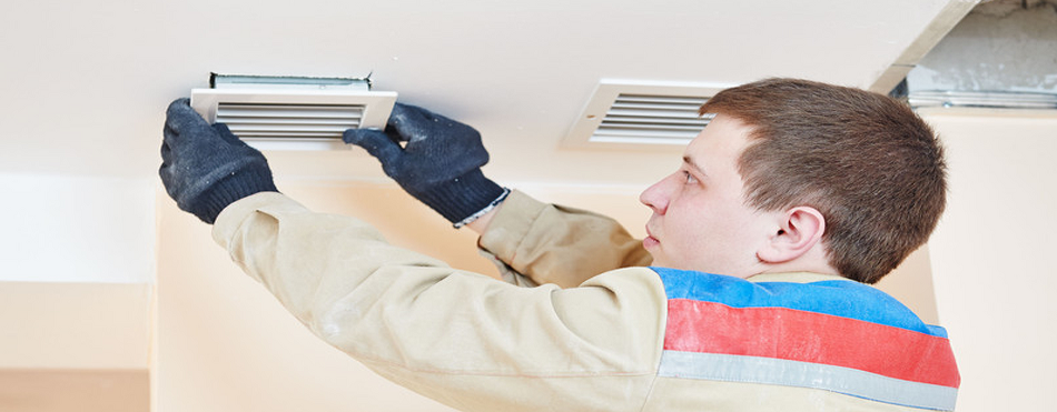 Picture of a certified technician dropping an air duct vent cover from the ceiling for cleaning