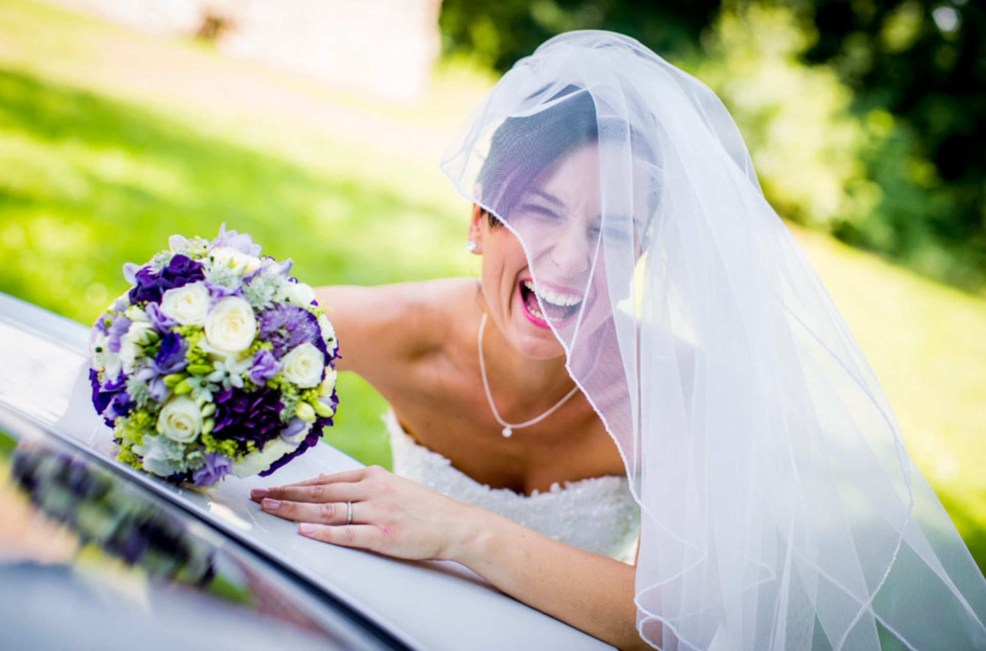 Beautiful laughing brunette bride wearing a  veil and holding flowers in her hand