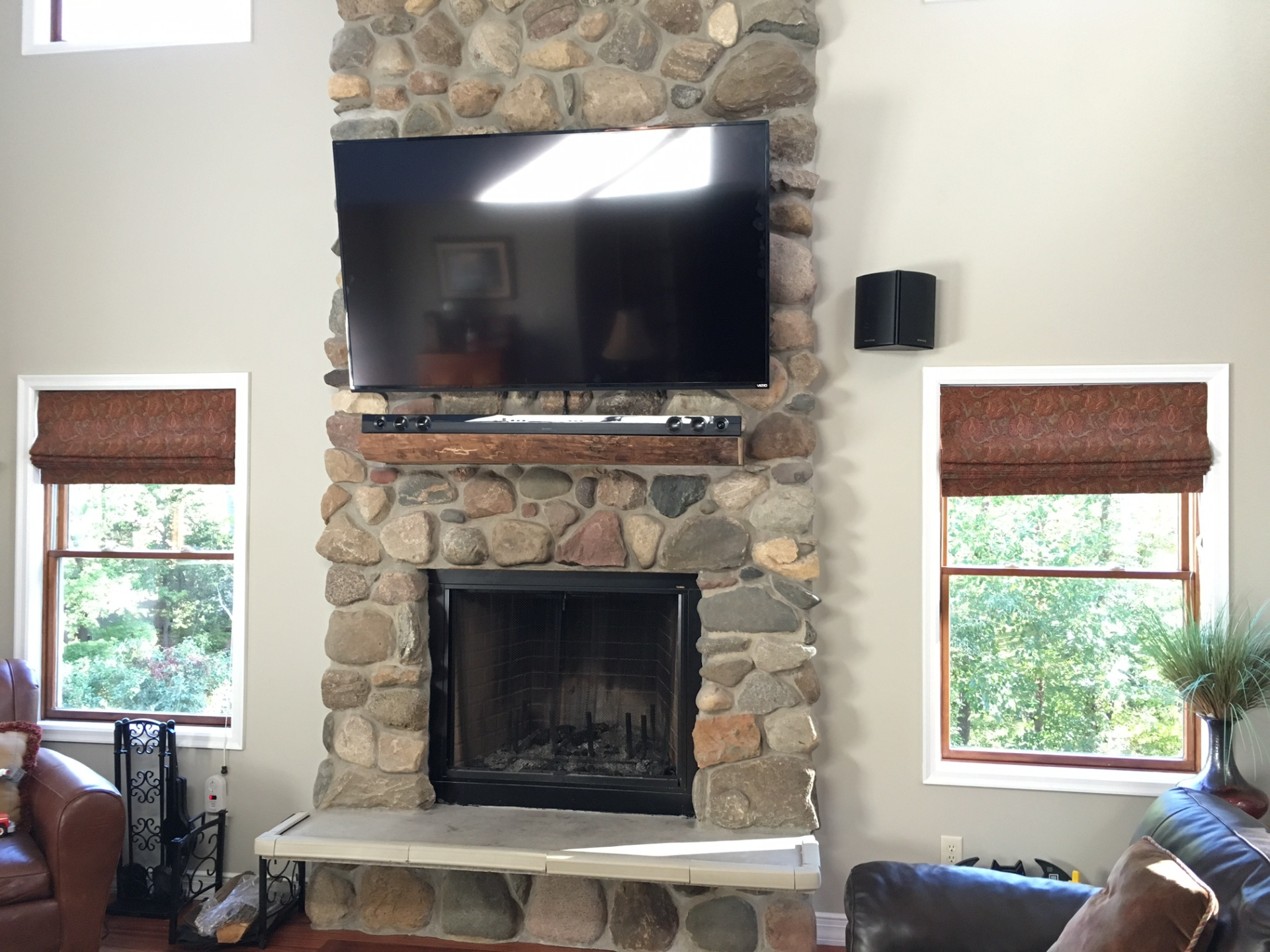 "70"" HDTV and Soundbar above Stone Fireplace"