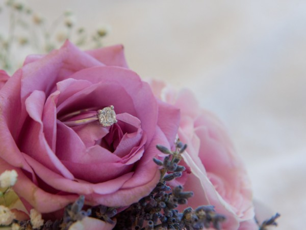 Engagement ring buried in pink rose bouquet
